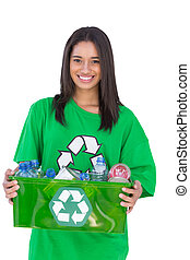 Enivromental activist holding box of recyclables and smiling on white background