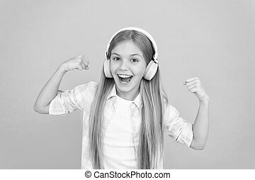 Enjoy a completely hands free listening experience. Little girl child listening to music. Happy little child enjoy music playing in headphones. Adorable music fan. Music makes her happy