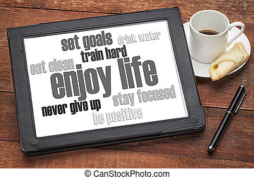 enjoy life - healthy lifestyle word cloud on a digital tablet with a cup of coffee