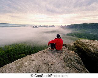 Enjoy life. Man in black trousers, jacket and dark cap sit on cliff's edge and looking to landscape