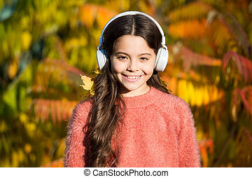 Enjoy music fall day. Autumn walks with nice songs. Educational and downloadable audio books for children. Kid girl relaxing near autumn tree with headphones. Music for autumn mood. Listening song