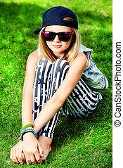 Modern girl teenager sitting on a grass.