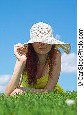 A beautiful girl on yellow dress and hat enjoying summer