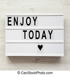 'Enjoy today' word on lightbox over white wooden background, from above. Top view, overhead, flat lay. Copy space.