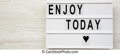 'Enjoy today' word on modern board over white wooden surface, from above. Top view, overhead, flat lay. Space for text.