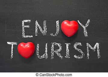 enjoy tourism phrase handwritten on school blackboard