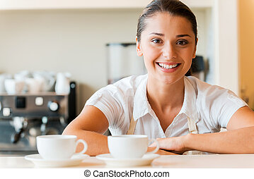 Enjoy your coffee! Beautiful young woman in apron looking at camera and smiling while standing at the bar counter in coffee shop