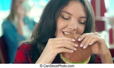 Close up of pretty girl eating hamburger