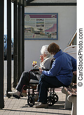 Disabled elderly lady in a wheelchair eating an ice cream and sitting next to a female carer in a bus shelter.