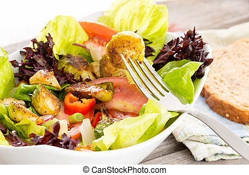 Enjoying a healthy vegetarian meal of sauteed brussels sprouts in a salad of leafy mixed greens, tomato and radish with a slice of wholewheat bread