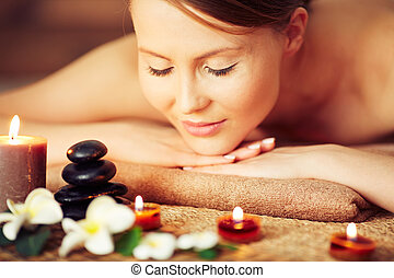 Enjoying aromatherapy - Woman relaxing among candles and ...