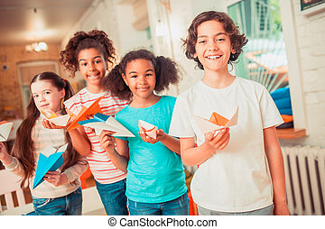 Happy kids holding their bright paper crafts