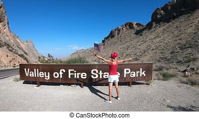 Enjoying at Valley of Fire Sign - Young tourist girl...