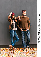 Enjoying autumn style. Beautiful young couple bonding to each other and looking away while leaning at the grey wall with fallen leaves laying around them