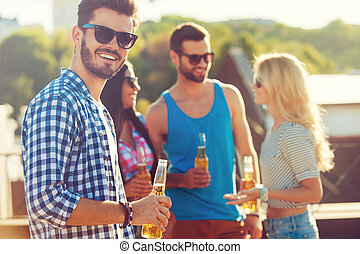 Enjoying beer with friends. Happy young man holding bottle of beer and looking at camera while three people talking to each other in the background