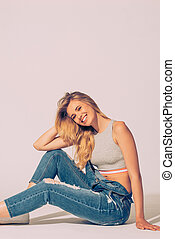 Enjoying casual style. Studio shot of beautiful young woman in jeans overall looking at camera and smiling while sitting on the floor