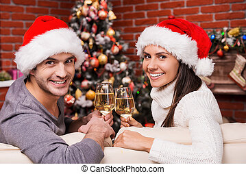 Enjoying Christmas time together. Happy young loving couple in Santa hats looking over shoulders and smiling while sitting on the couch together and drinking wine with Christmas Tree in the background