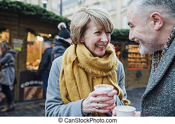 Enjoying Coffee At The Christmas Market - Mature couple are...