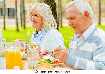 Enjoying dinner outdoors. Senior couple enjoying meal together while sitting at the dining table outdoors