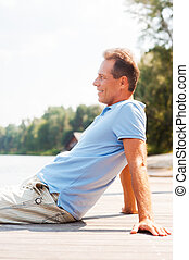 Enjoying doing nothing. Side view of cheerful mature man looking away and smiling while sitting at the quayside