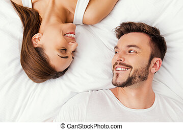 Enjoying every moment together. Top view of beautiful young loving couple lying in bed together and looking at each other