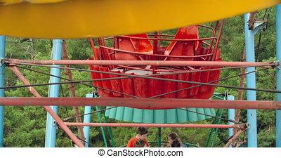 Enjoying Ferris Wheel Ride - Four kids pointing at camera as...