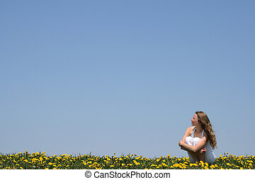 Young woman enjoying fresh air and sun in a flowering field.
