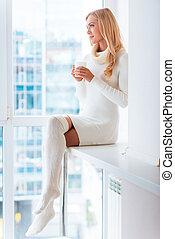 Enjoying fresh coffee at home. Beautiful young woman in warm...