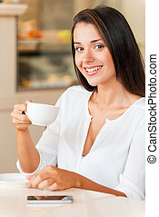 Enjoying fresh coffee. Beautiful young woman drinking coffee and smiling while sitting in coffee shop
