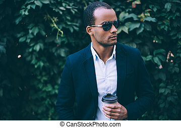 Enjoying fresh coffee. Handsome young African man in sunglasses holding coffee cup and looking away while standing against green plant background outdoors