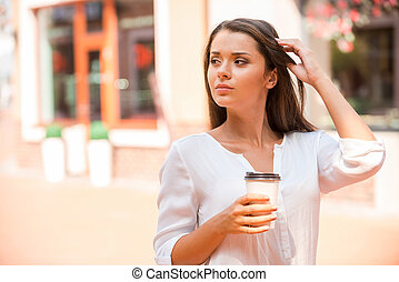 Enjoying fresh coffee on the Go. Beautiful young woman holding coffee cup and looking away while standing outdoors