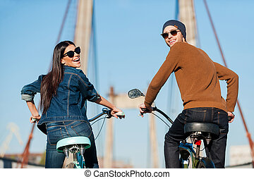 Enjoying fun ride. Rear view of beautiful young couple riding bicycles and looking over shoulder with smile