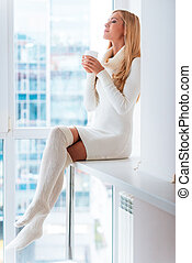 Enjoying good day at home. Beautiful young blond hair woman...