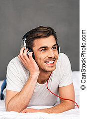 Enjoying good music in bed. Cheerful young man adjusting his headphones and looking away with smile while lying on front in bed against grey background