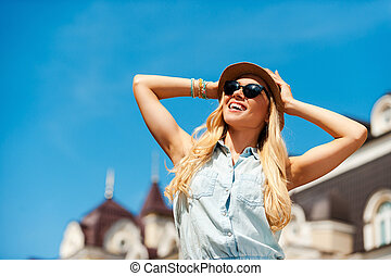 Enjoying great day in the city. Low angle view of smiling young woman holding head in hands and looking away while standing outdoors