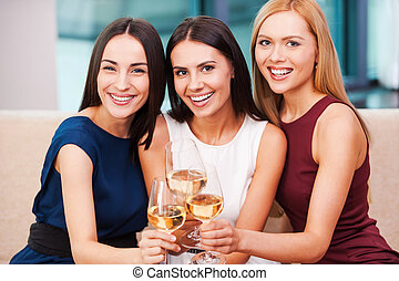 Enjoying great time together. Three beautiful young women in evening gown sitting on the couch and holding glasses with wine