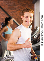 Enjoying healthy lifestyle. Handsome young man showing his thumb up and smiling while walking on a treadmill with woman running in the background