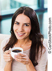 Enjoying her coffee break. Top view of attractive young woman holding cup with coffee and smiling while relaxing on the couch at home