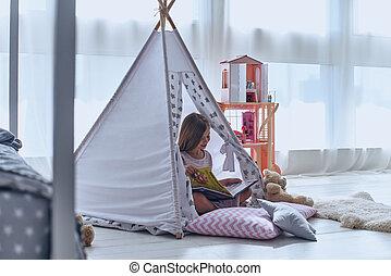 Enjoying her little world. Lovely little girl reading a book...