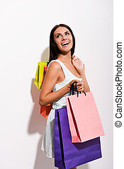 Enjoying her shopping. Excited young woman in dress carrying colorful shopping bags and looking over shoulder with smile while standing against white background