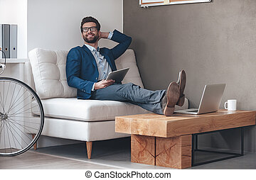 Enjoying his working day. Handsome cheerful young man keeping legs on table and looking away with smile while sitting on the couch in office