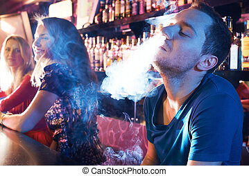 Enjoying hookah - Portrait of young man letting smoke out of...