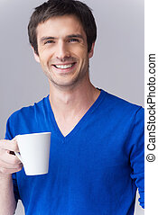 Enjoying hot drink. Handsome young man in blue sweater holding coffee cup and smiling while standing against grey background