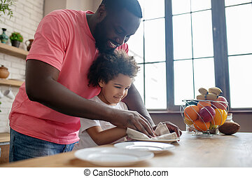 Tall dark-skinned man in a pink tshirt and his kid wiping the plate and feeling good