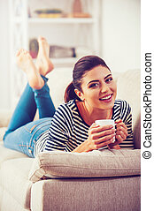 Enjoying leisure time at home. Beautiful young woman holding coffee cup and smiling while lying on the couch at home