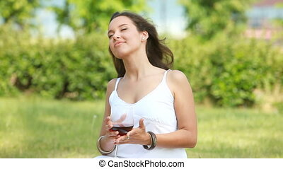 Pretty young woman spending time outdoors, drinking wine and enjoying sunny weather