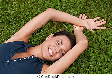 Enjoying life - woman lying in grass