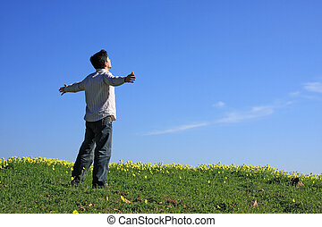 Young man looking to the sky with his arms outstretched