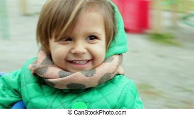 Enjoying motion - Little girl having a playground ride...