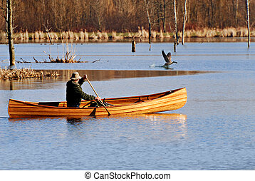 Man paddling canoe in environmental conservation area